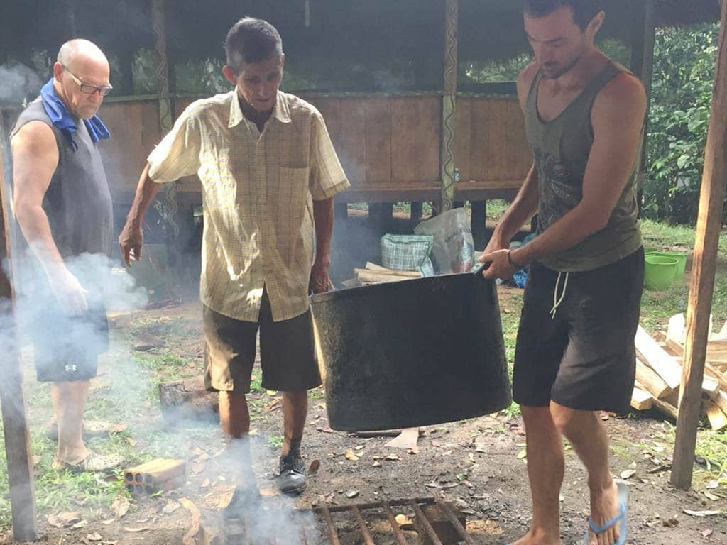 don joel carrying ayahuasca medicine with guest at Rainforest Healing Center